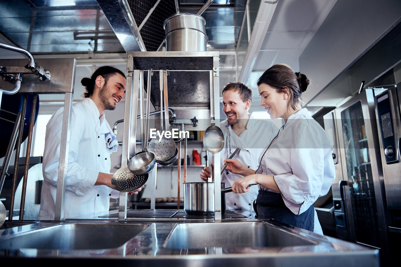 men, adult, indoors, young men, young adult, standing, mid adult, occupation, group of people, food and drink, business, males, commercial kitchen, mid adult men, smiling, holding, waist up, people, teamwork, chef, preparation, coworker