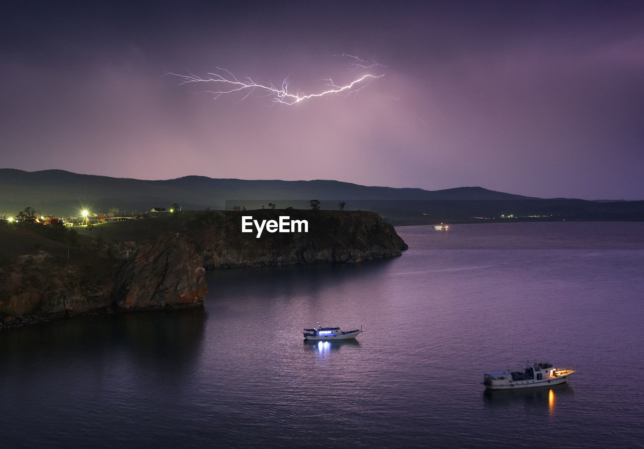 Boats Sailing In Sea During Lightning In Sky At Dusk