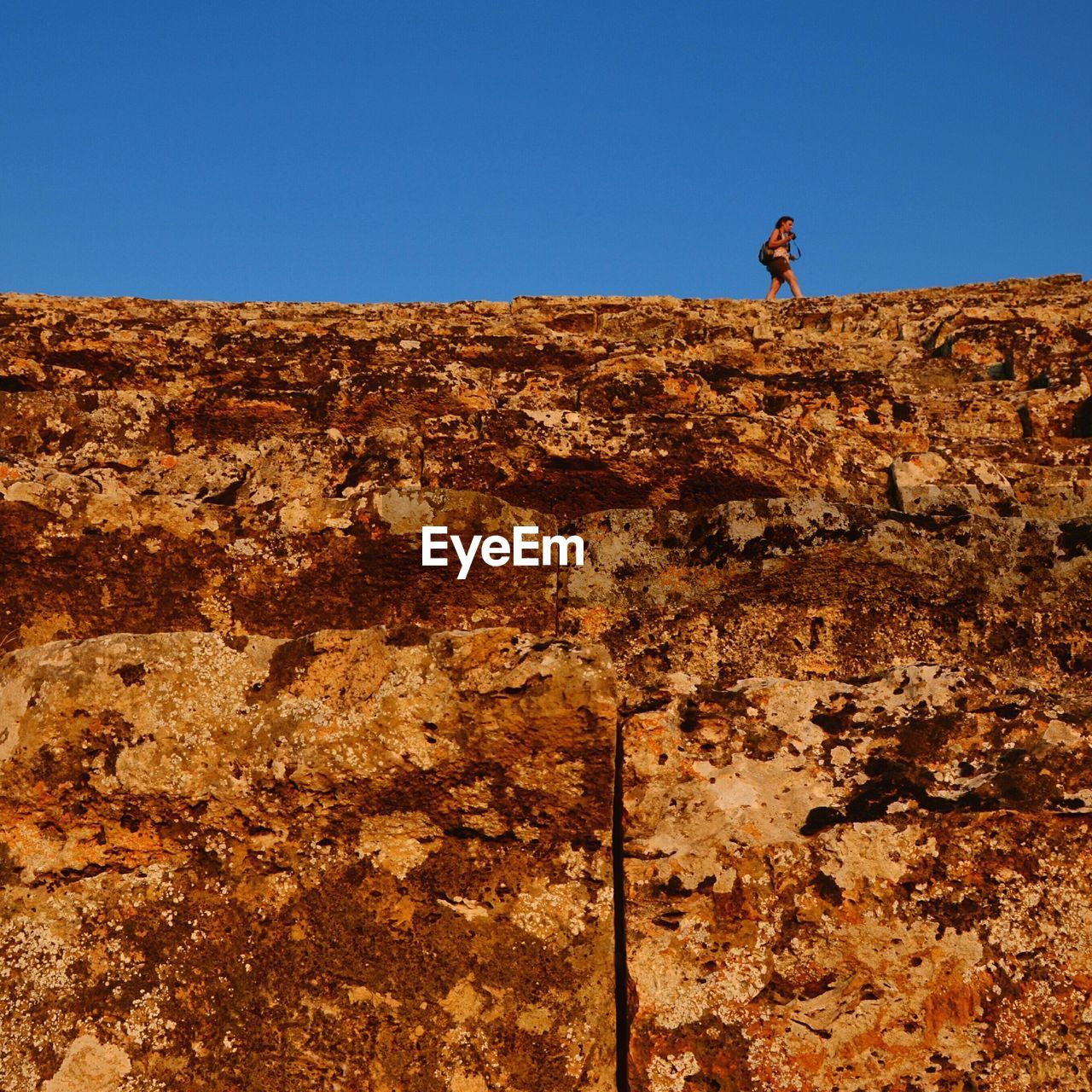 Low angle view of woman walking on rock against clear blue sky