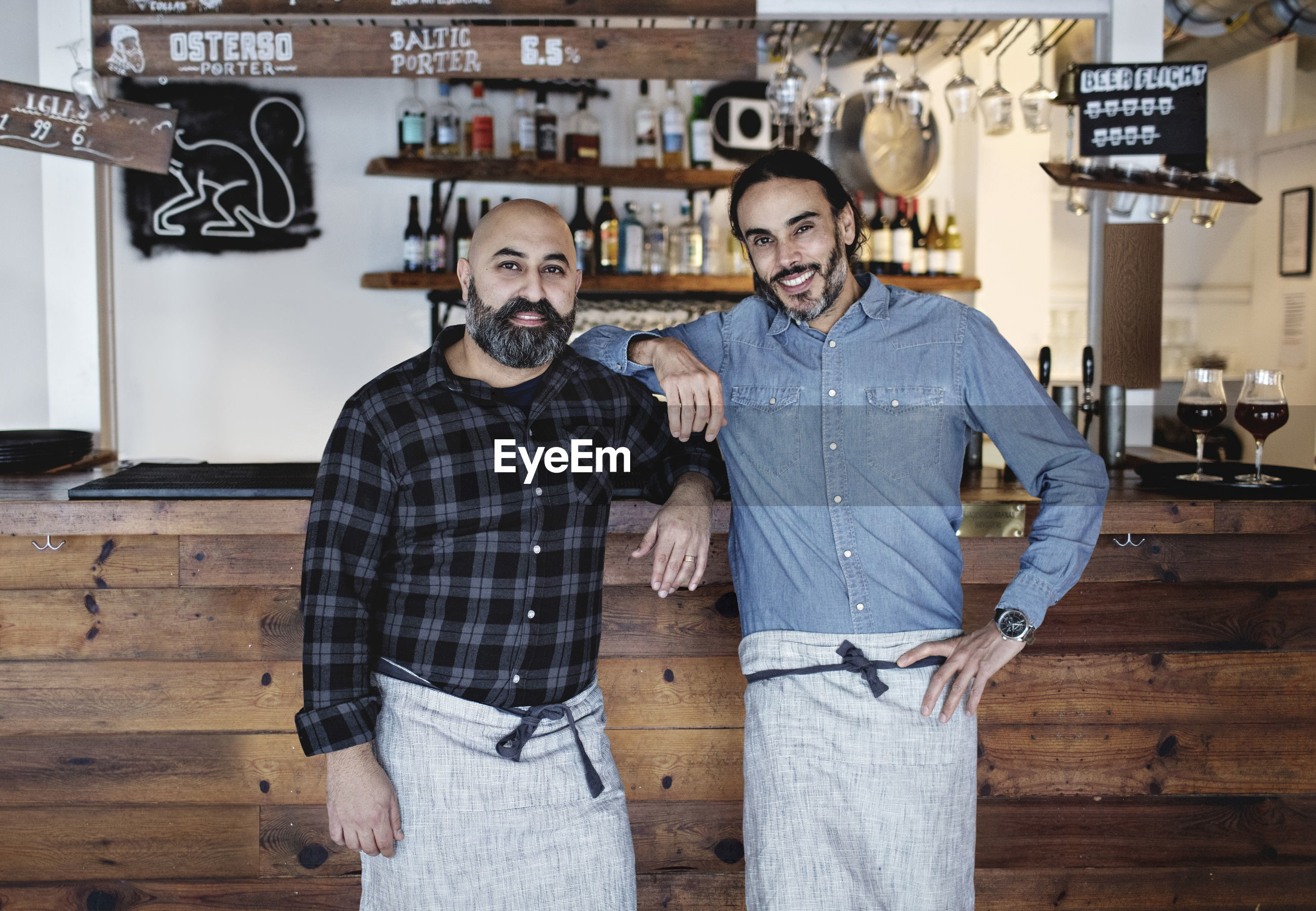 Portrait of male partners standing at bar counter