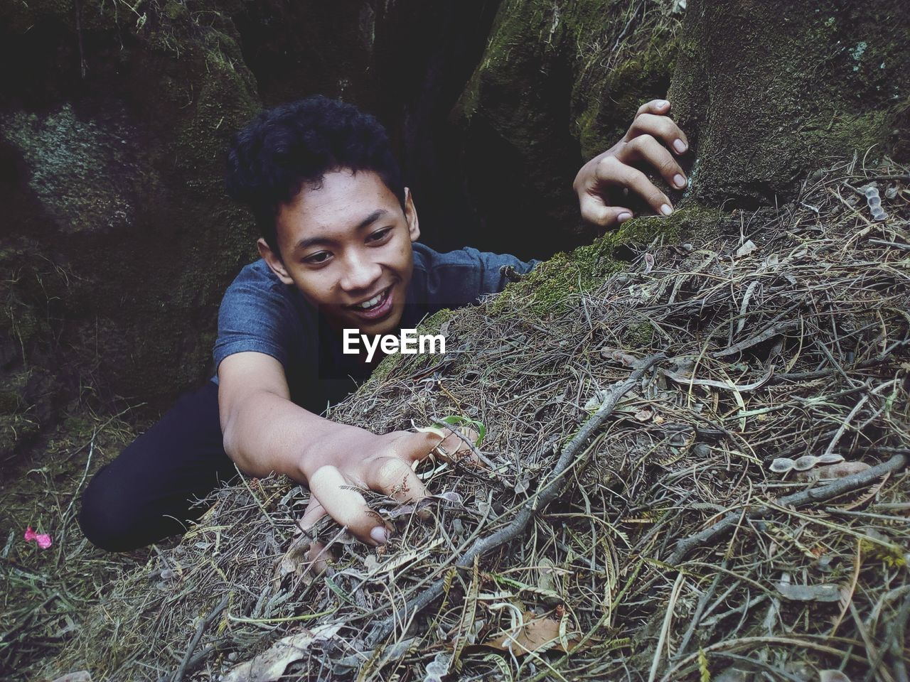 High Angle View Of Smiling Young Man In Forest