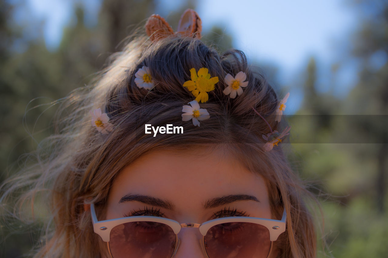 Close-Up Of Woman Wearing Sunglasses And Flowers