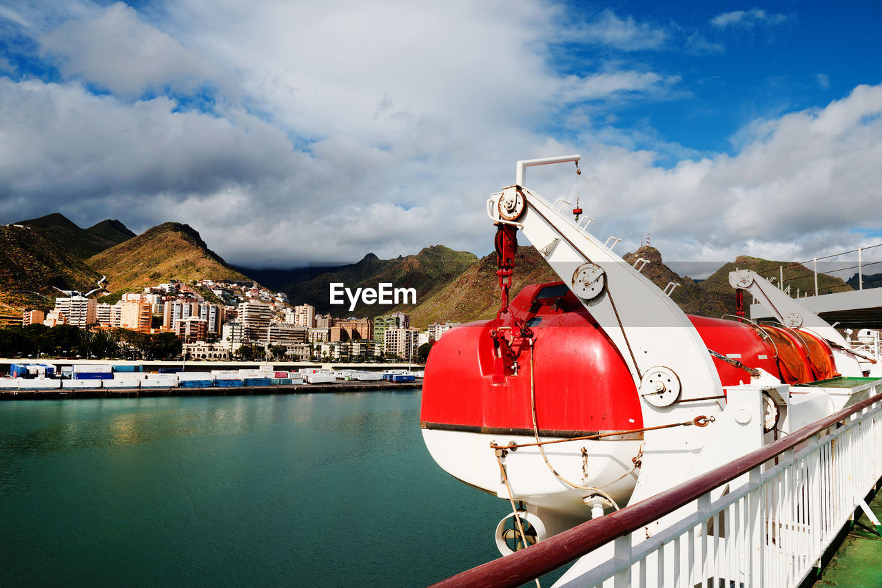 Lifeboat on cruise ship in sea against cloudy sky at canary islands