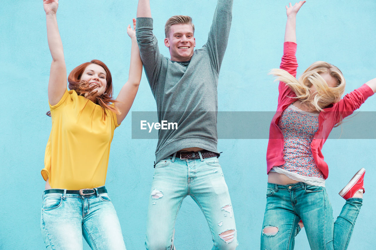 Young Friends With Arms Raised Jumping Against Wall