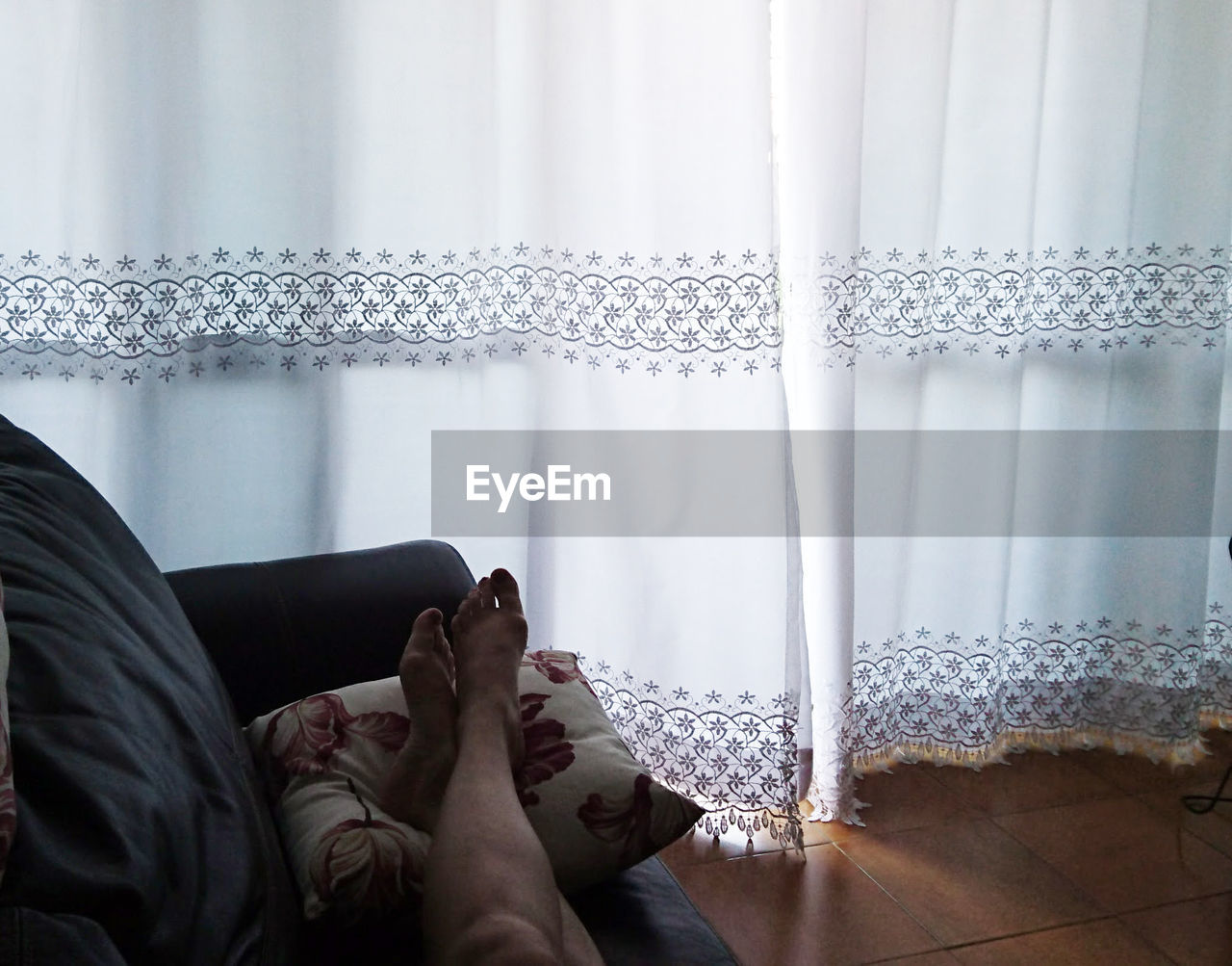 curtain, indoors, real people, window, low section, human leg, relaxation, lifestyles, one person, human body part, body part, lying down, home interior, barefoot, day, adult, bed, women, leisure activity, human foot, flooring
