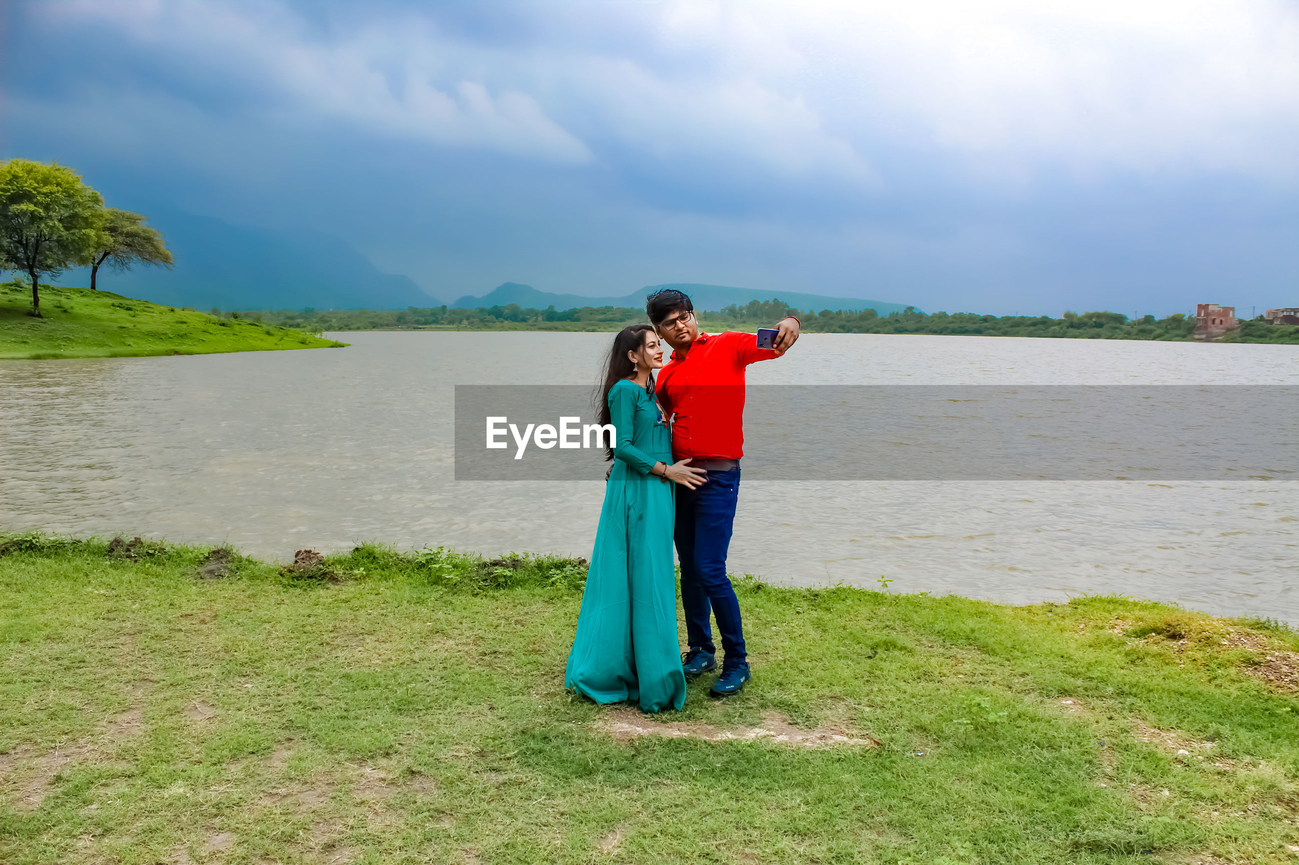 Couple taking selfie with mobile phone while standing on grass by lake against sky