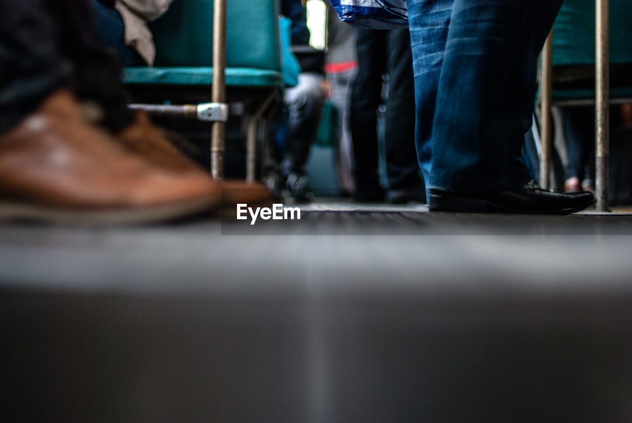low section, human leg, standing, selective focus, real people, human body part, shoe, indoors, two people, men, day, close-up, people