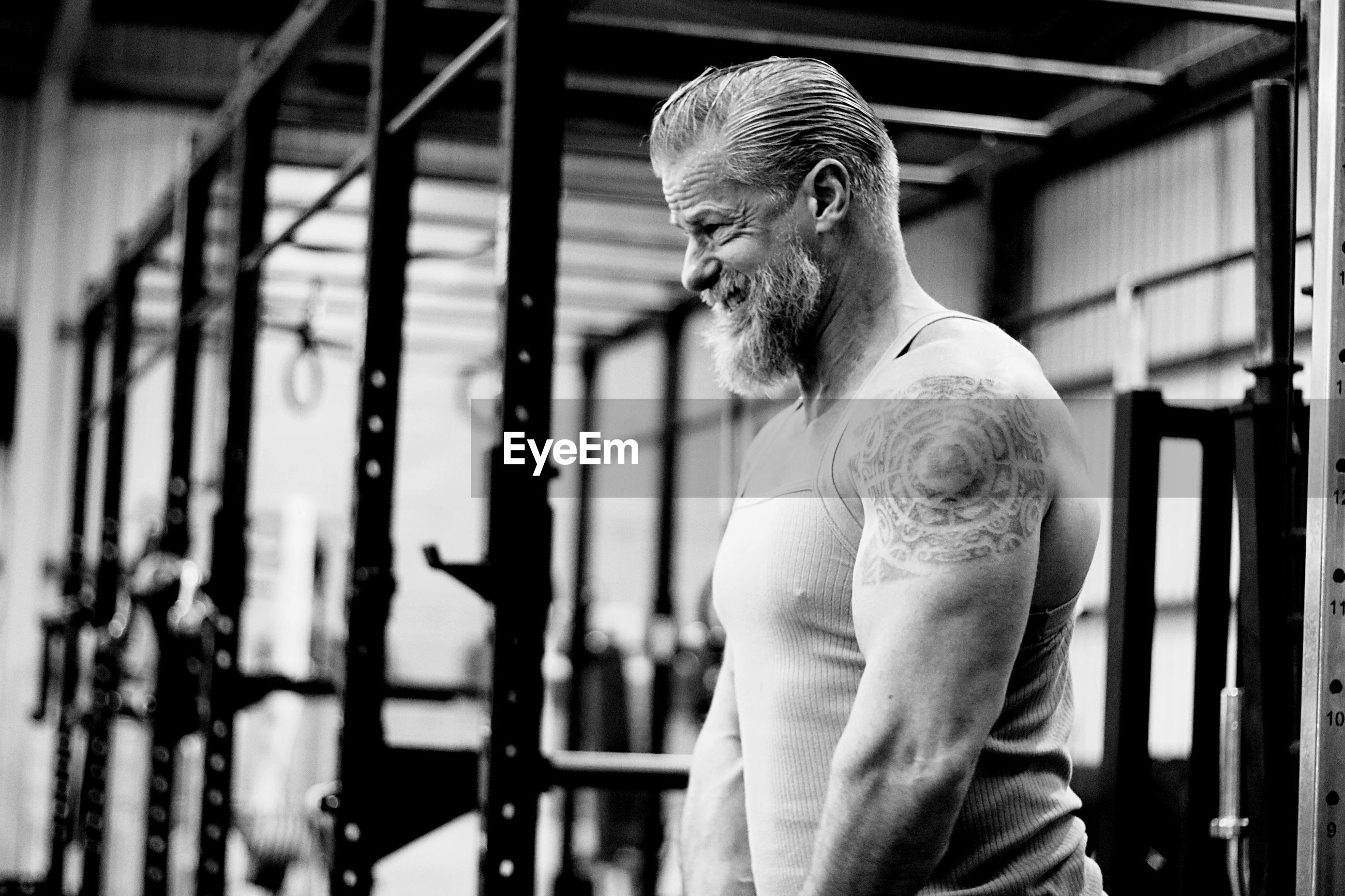 Side view of mature man standing in gym