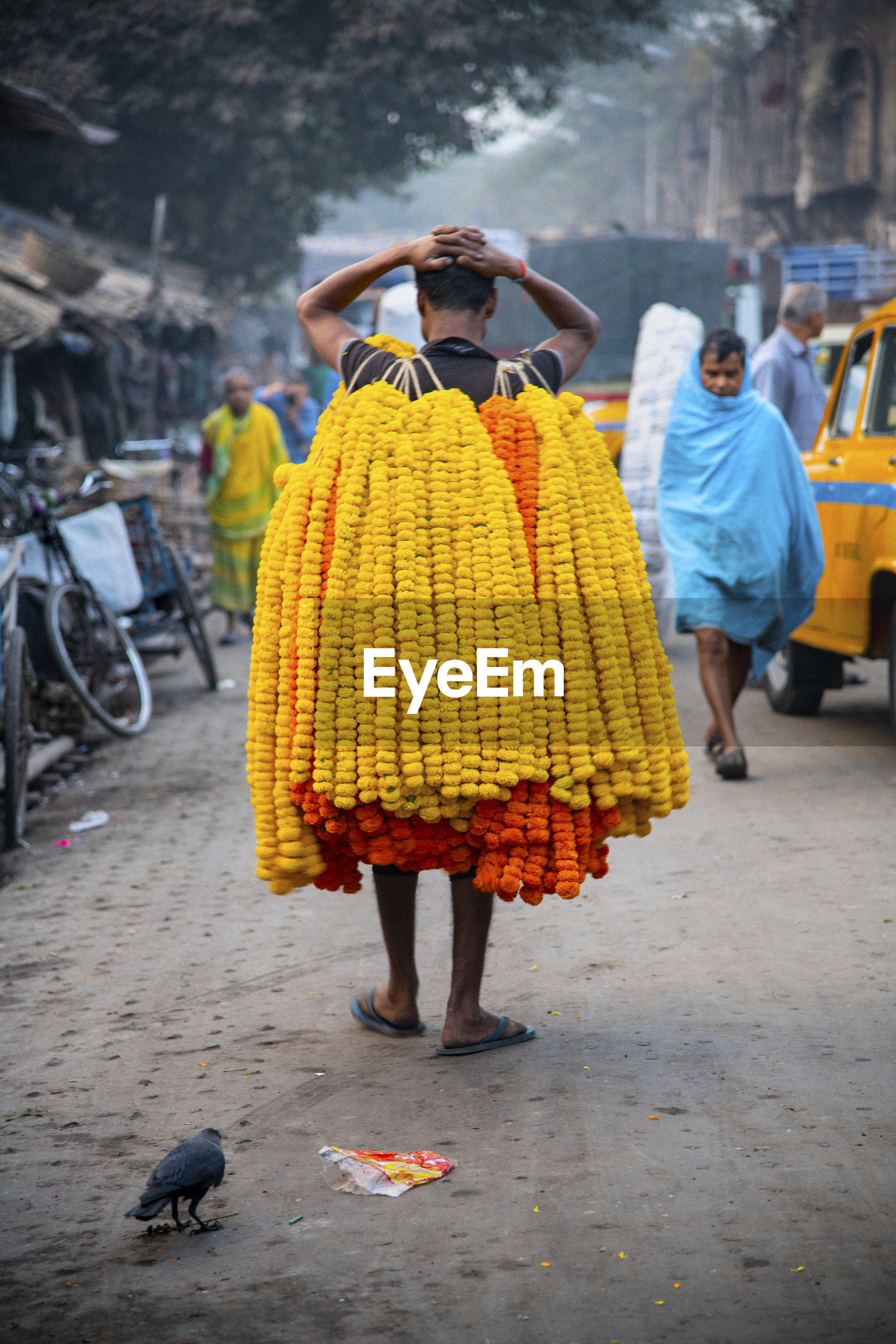 REAR VIEW OF A WOMAN HOLDING YELLOW UMBRELLA ON STREET