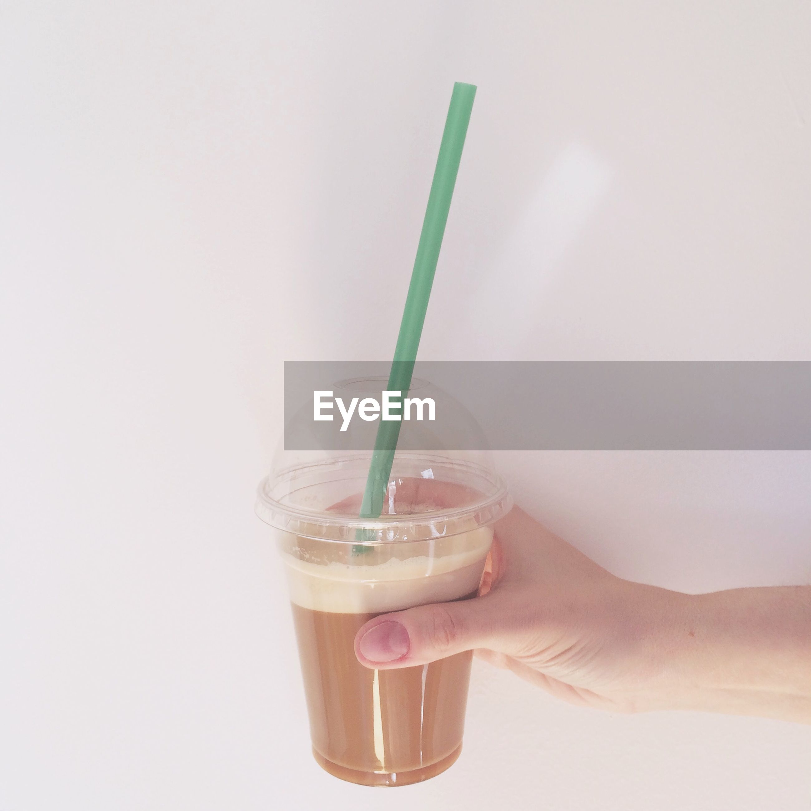 Cropped hand holding iced coffee against wall at home