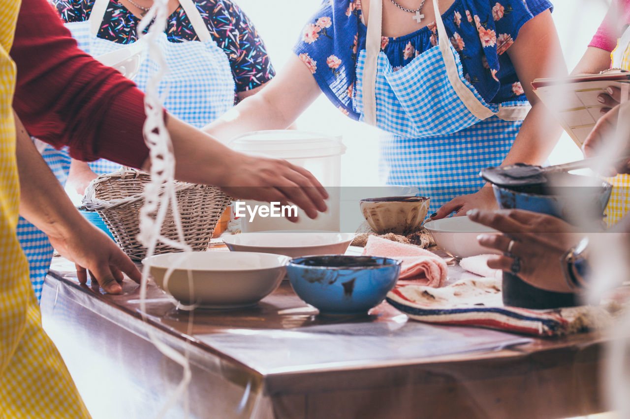 Midsection of women preparing food at table