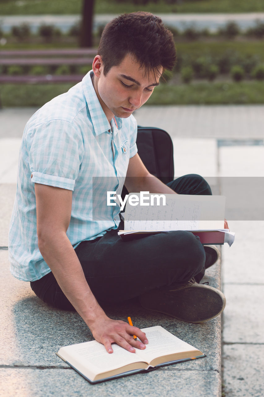 Young University Student Studying While Sitting On Floor