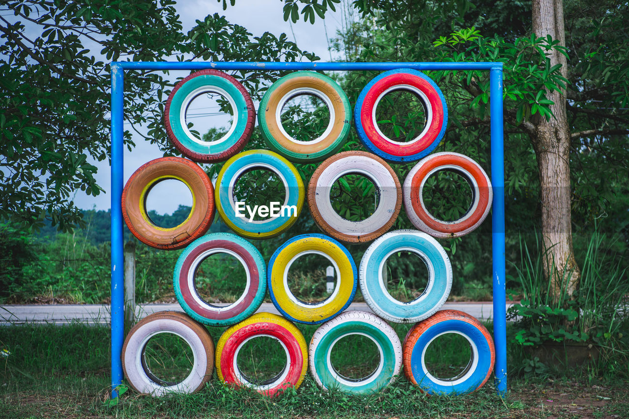 tree, plant, childhood, multi colored, shape, day, nature, playground, circle, blue, park, geometric shape, park - man made space, outdoor play equipment, outdoors, design, grass, metal, side by side, wheel