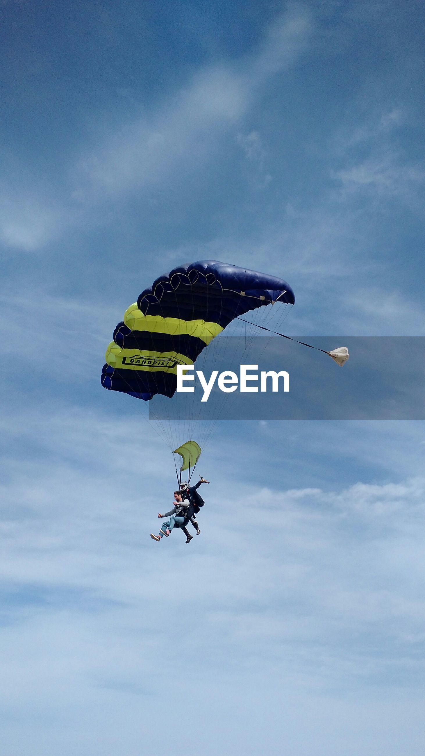 transportation, sky, low angle view, mode of transport, cloud - sky, flying, mid-air, extreme sports, leisure activity, adventure, parachute, cloudy, travel, on the move, cloud, text, air vehicle, day, unrecognizable person