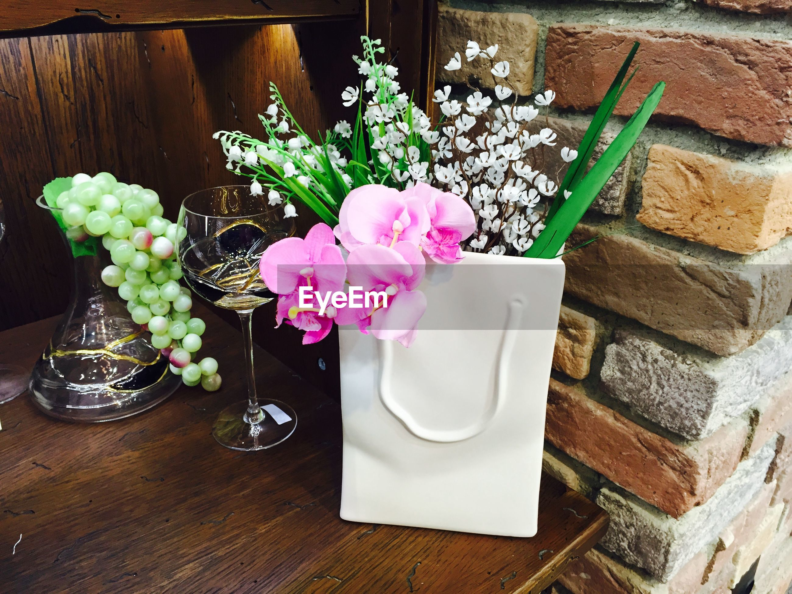 Flower vase and wineglass on table