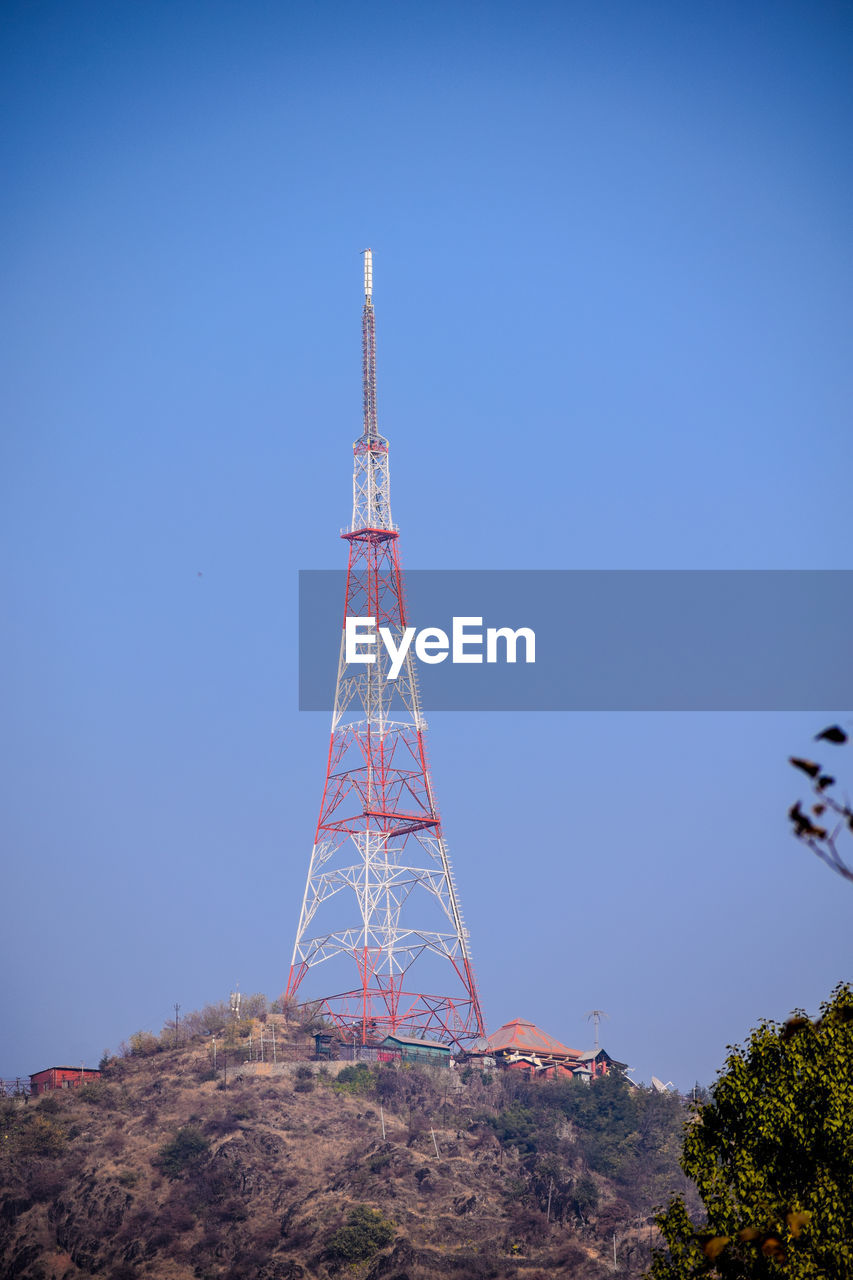 Low angle view of communication tower against clear blue sky