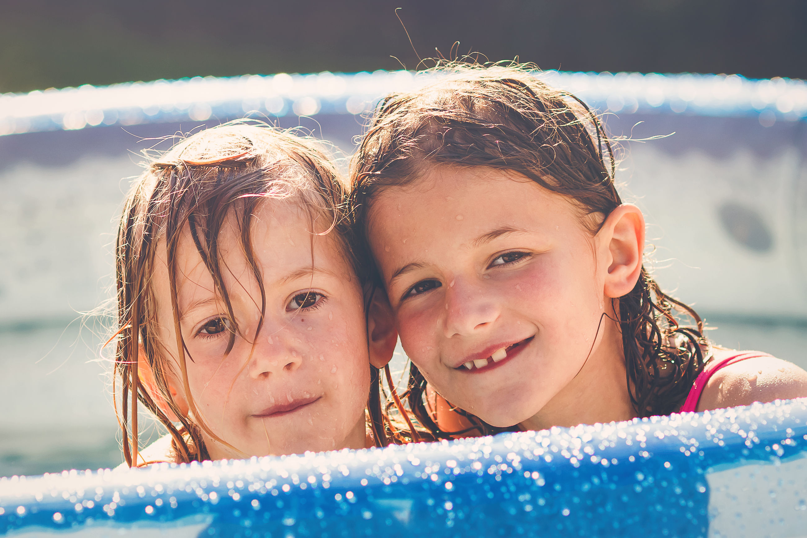 Close-up portrait of cute siblings in wading pool