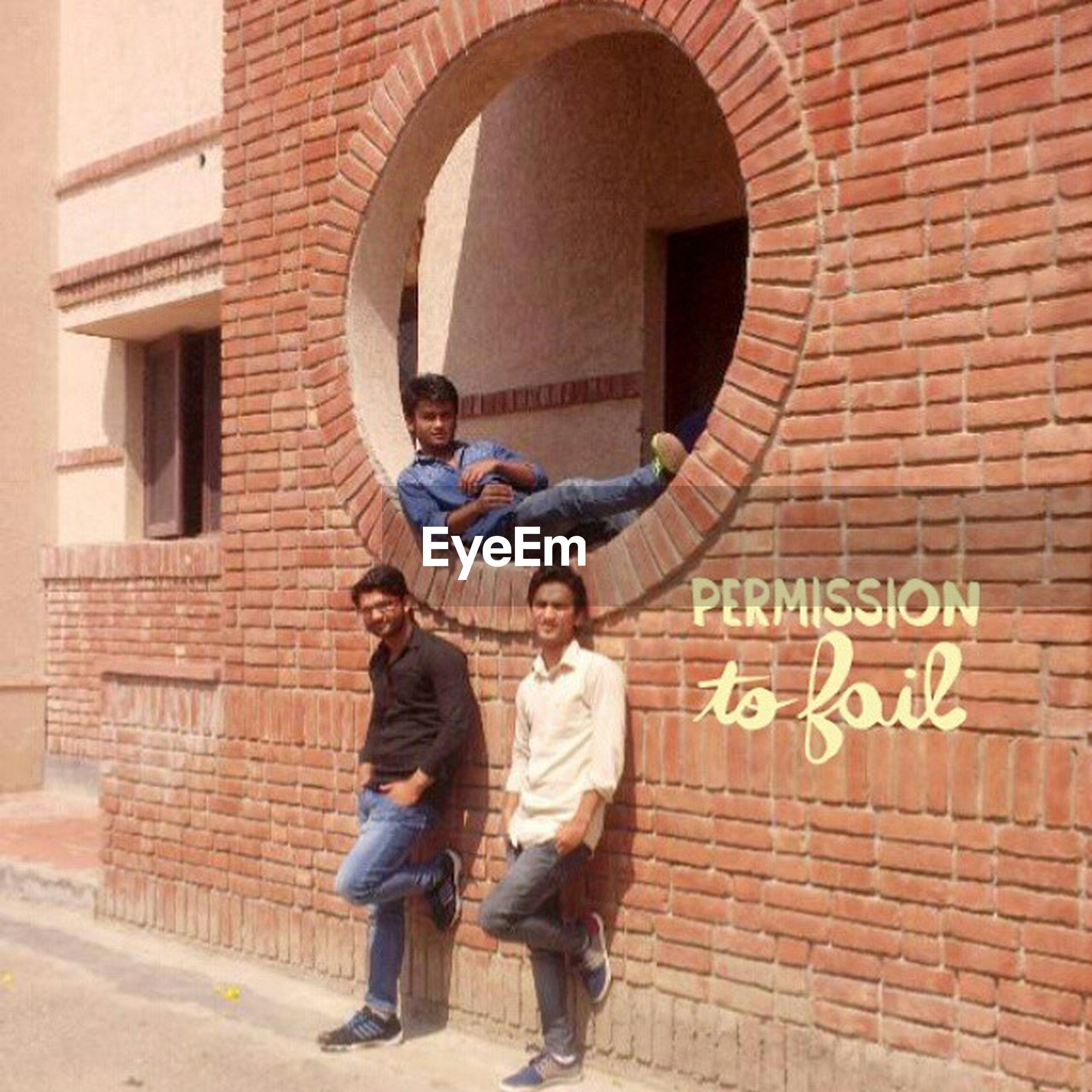 building exterior, full length, architecture, built structure, lifestyles, leisure activity, casual clothing, brick wall, text, men, young adult, communication, front view, person, wall - building feature, young men, standing, holding