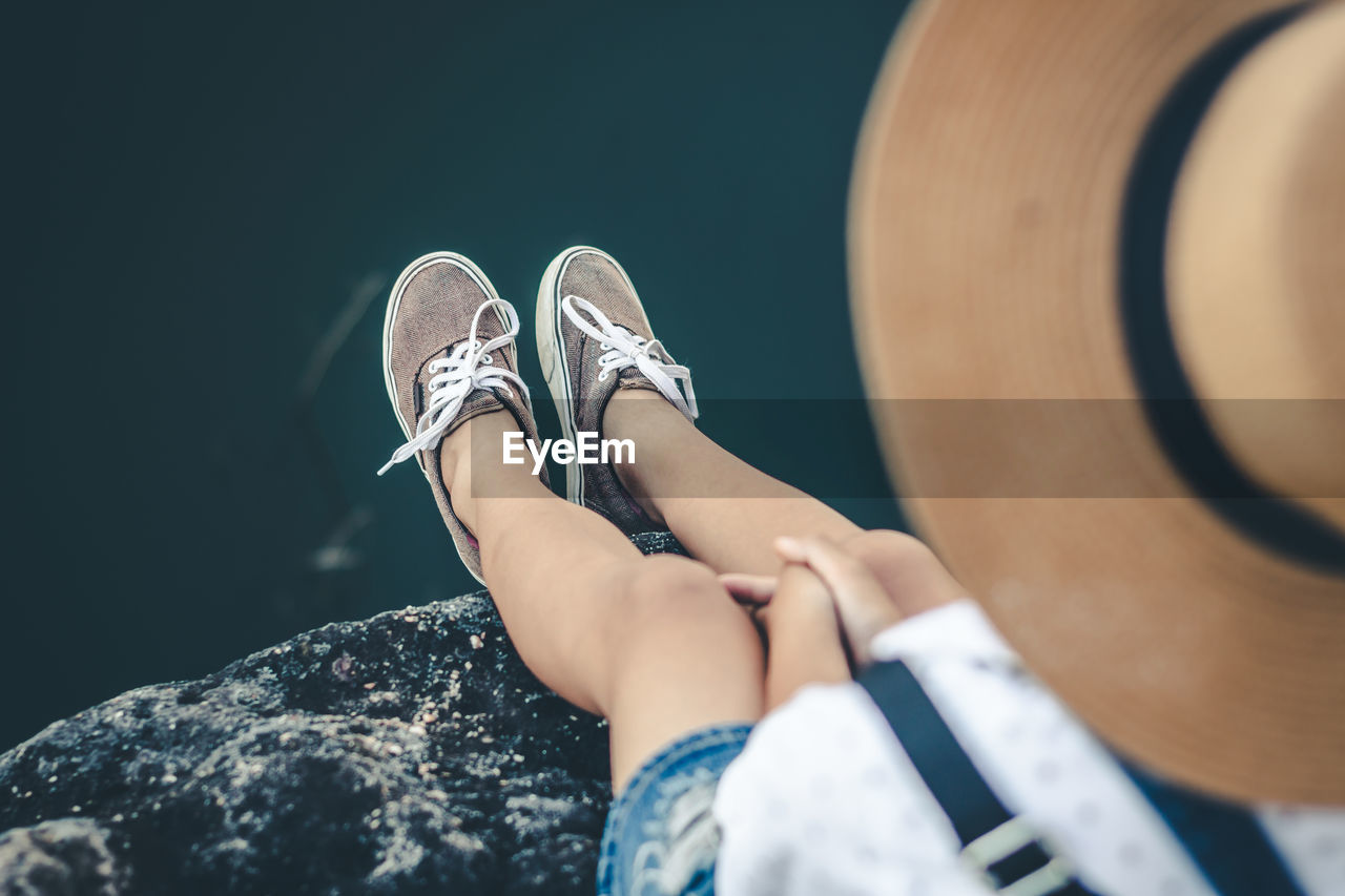 shoe, low section, human body part, real people, body part, one person, selective focus, lifestyles, leisure activity, human leg, day, close-up, personal perspective, canvas shoe, focus on foreground, sitting, outdoors, solid, nature, human foot