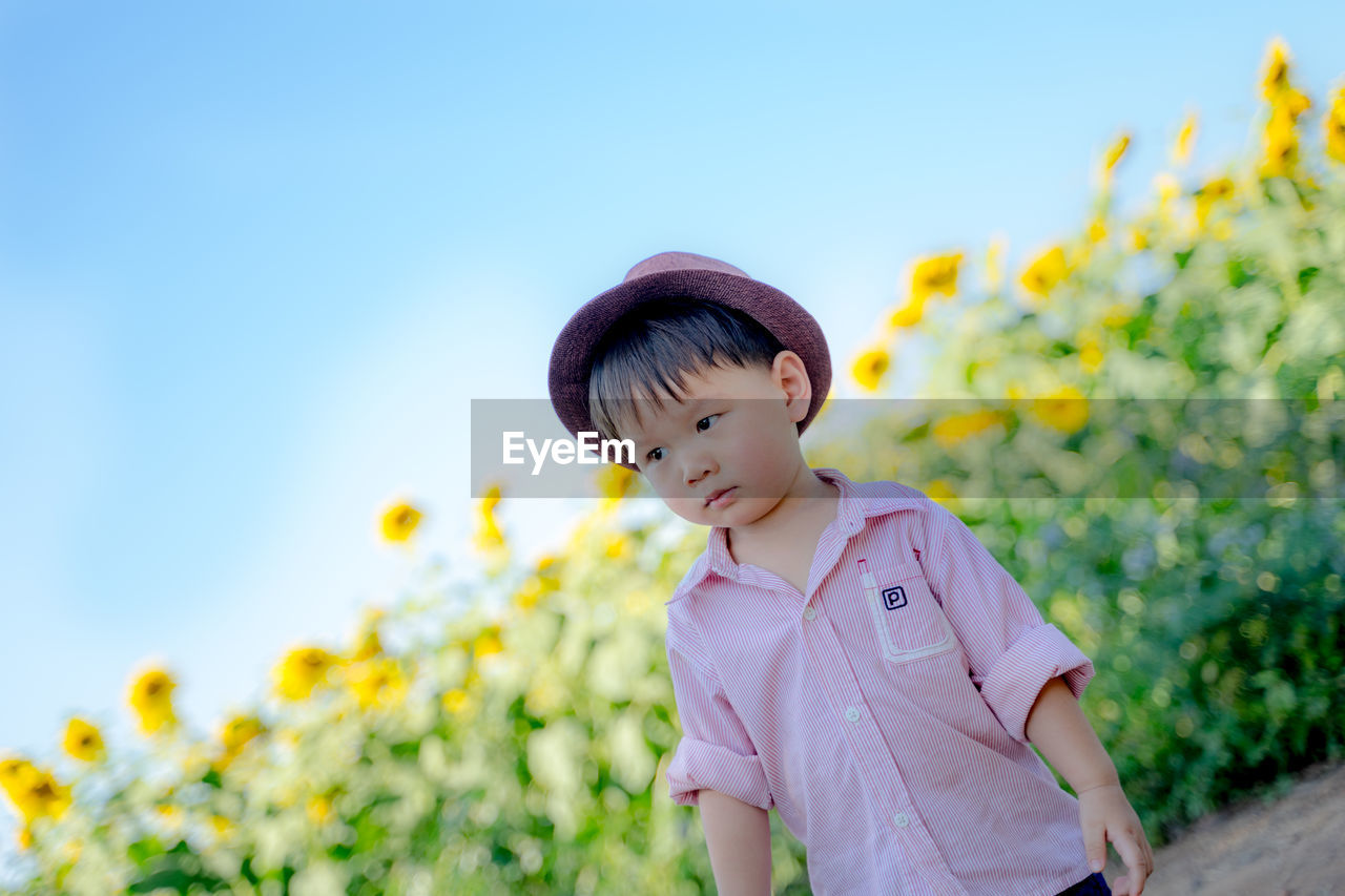 Cute baby boy in hat standing on field