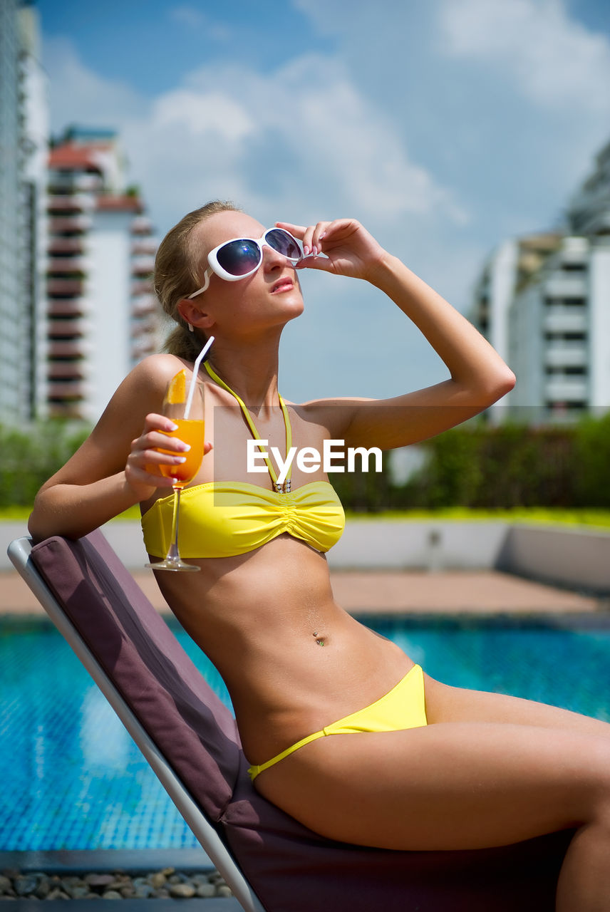 water, fashion, sunglasses, lifestyles, one person, glasses, day, clothing, young adult, pool, real people, young women, nature, leisure activity, swimming pool, focus on foreground, swimwear, adult, women, beautiful woman, outdoors