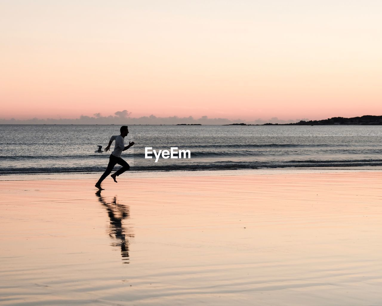 Side view of man running at beach against sky during sunset