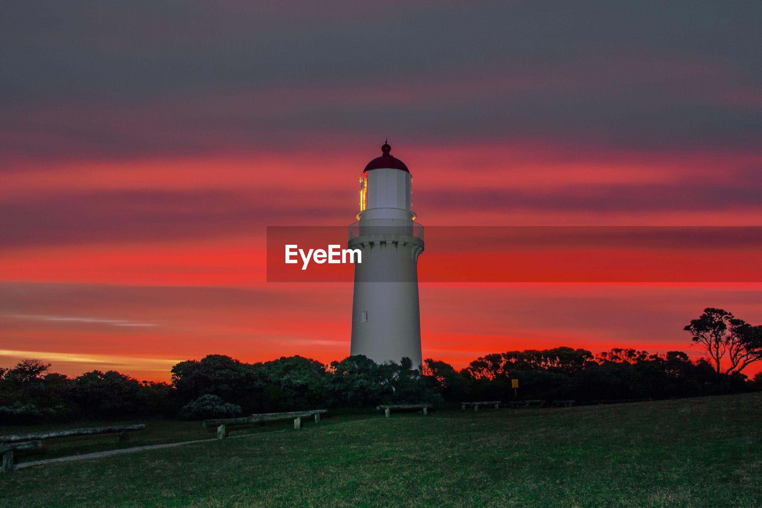 Lighthouse at distance on landscape against sky
