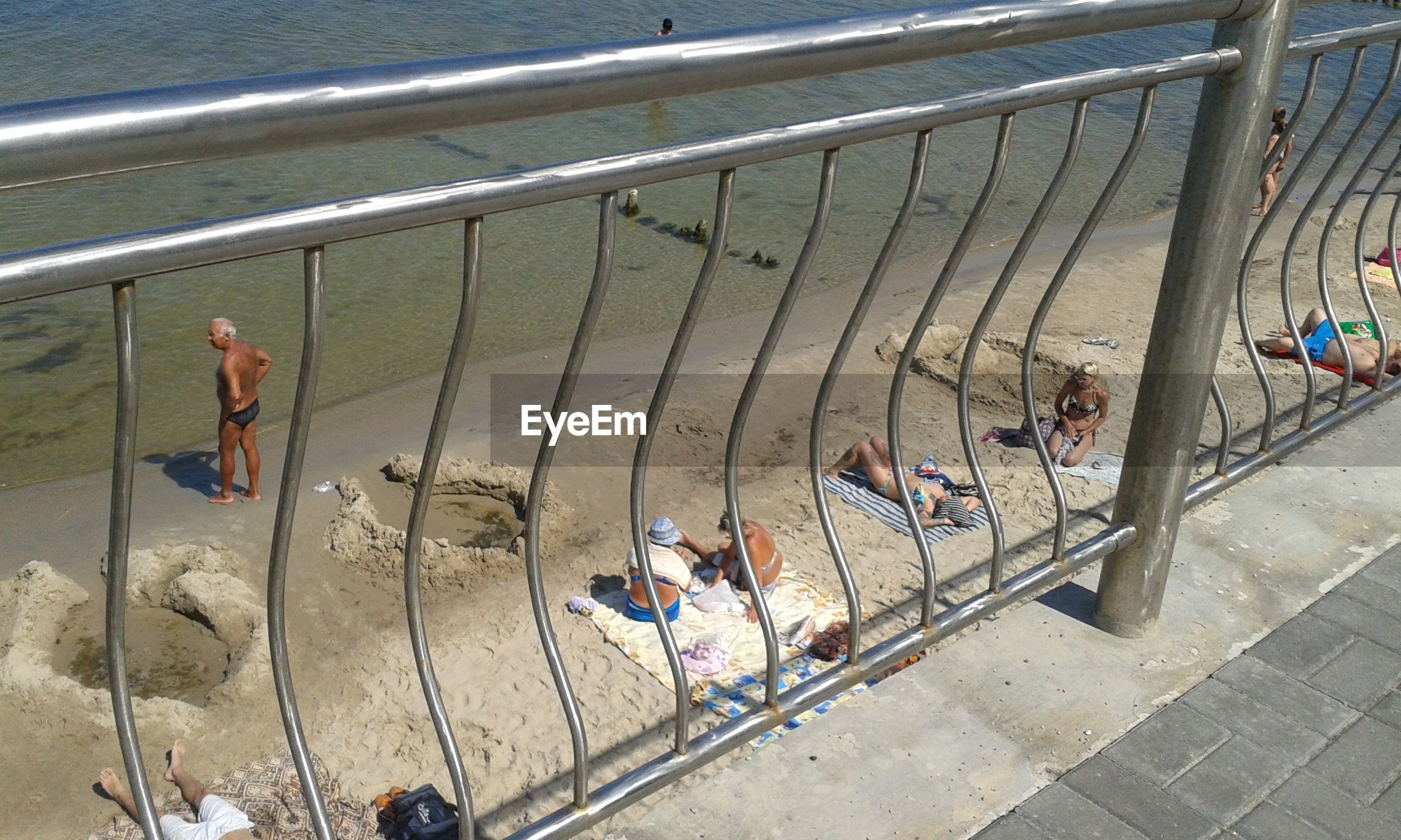 high angle view, lifestyles, water, leisure activity, men, person, sitting, large group of people, railing, day, togetherness, beach, outdoors, relaxation, sunlight, sand, sea, full length, shore