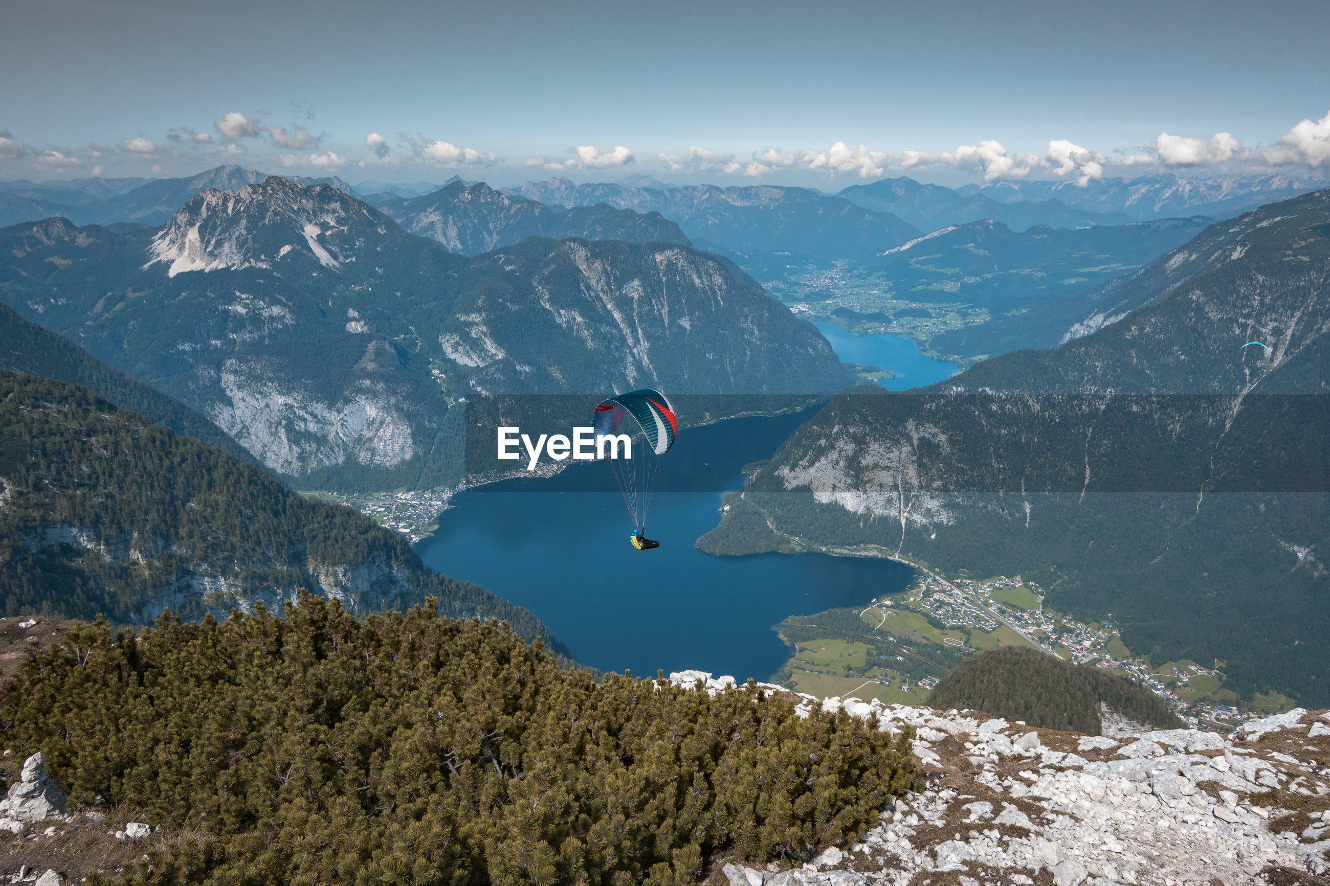 High angle view of person paragliding on mountain against sky