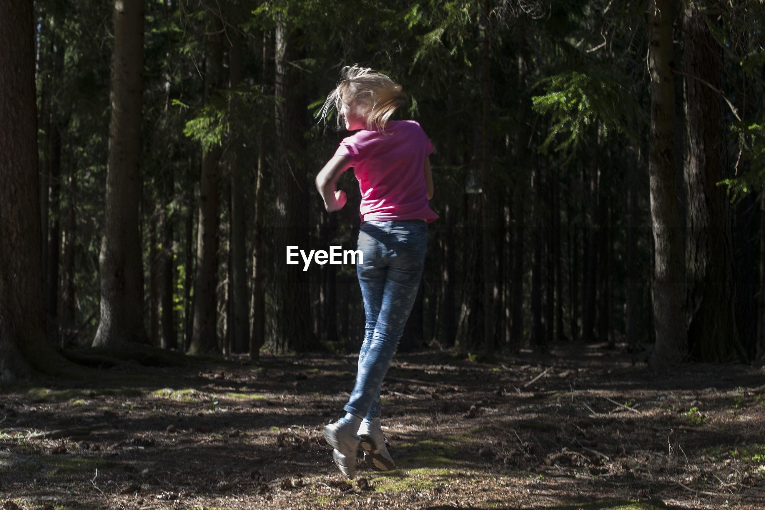 Full length of girl jumping in forest against trees