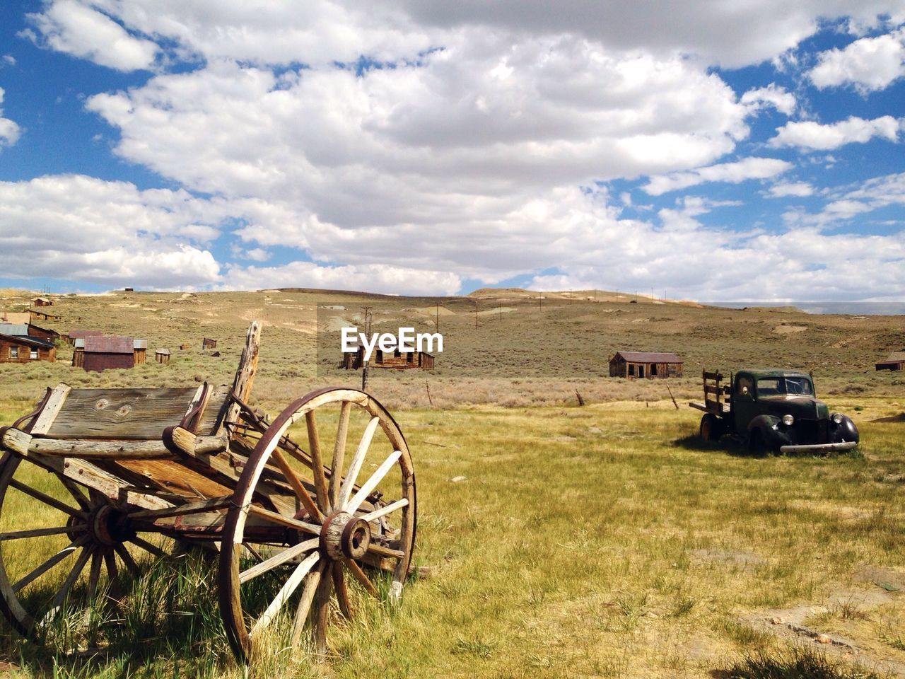 Abandoned Cart And Car On Grassy Field Against Cloudy Sky