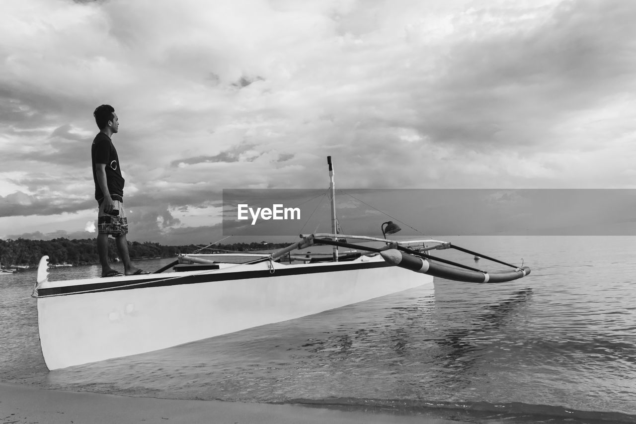 MAN STANDING ON BOAT AGAINST SEA