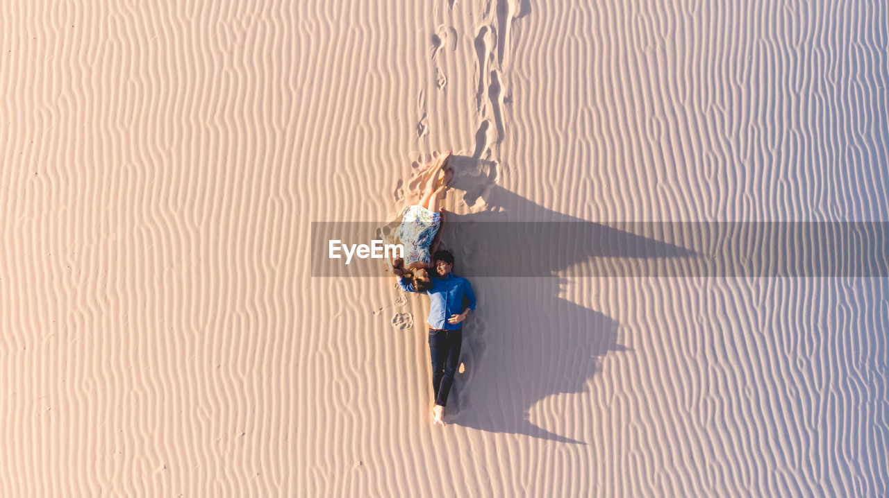 High Angle View Of Couple Lying On Sand At Desert