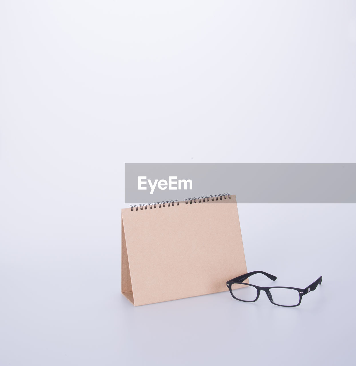 copy space, studio shot, white background, indoors, still life, no people, eyeglasses, close-up, paper, cut out, glasses, communication, cardboard, single object, two objects, technology, connection, note pad, creativity, blank