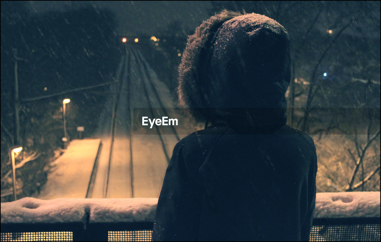Rear View Of Person Standing On Footbridge Over Snow Covered Railroad Tracks At Night