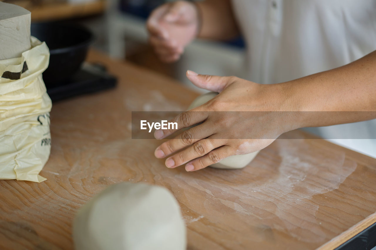 Midsection of woman kneading clay on table