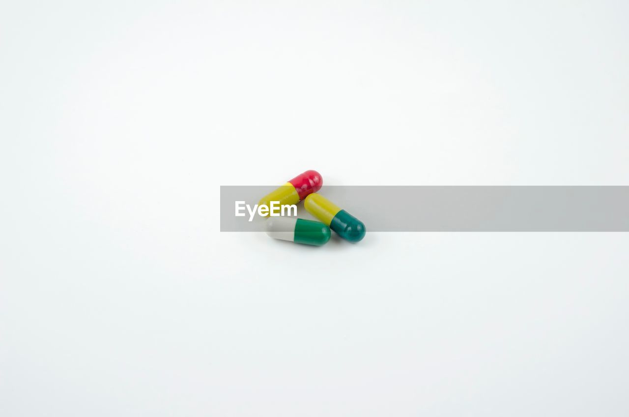 High angle view of capsules against white background