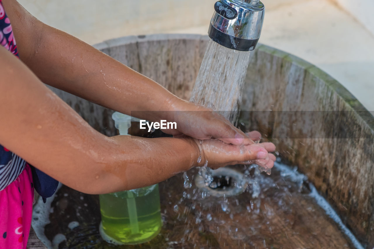 water, real people, human body part, one person, human hand, lifestyles, body part, motion, washing, hand, nature, food and drink, focus on foreground, domestic room, leisure activity, hygiene, domestic bathroom, human leg, outdoors, running water, human foot, finger, flowing water