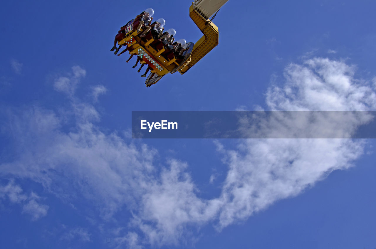 Low Angle View Of People Enjoying Ride At Amusement Park Against Sky