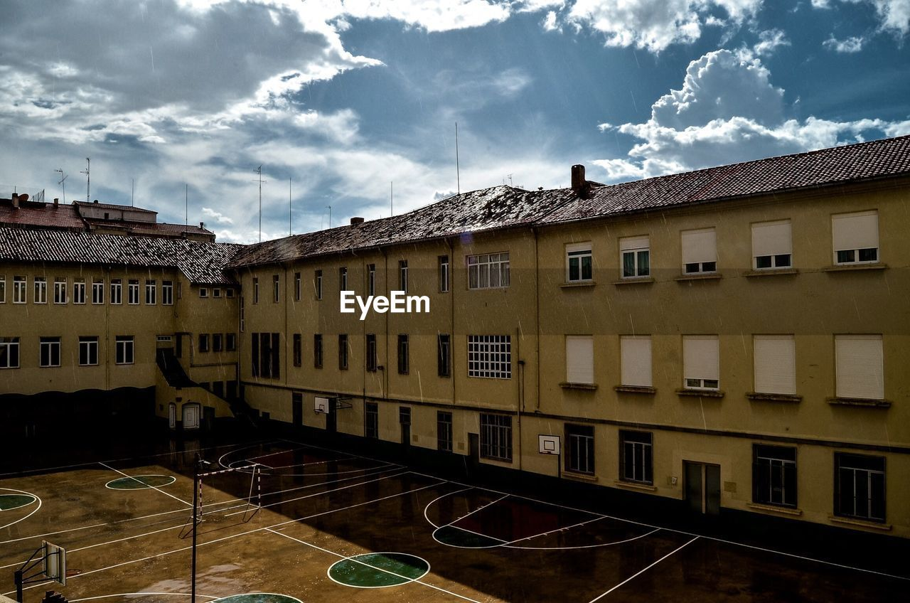 High Angle View Of Building And Basketball Court Against Cloudy Sky