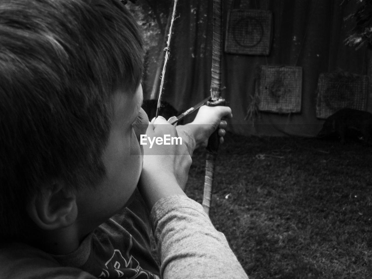 Close-Up Of Boy Aiming At Target