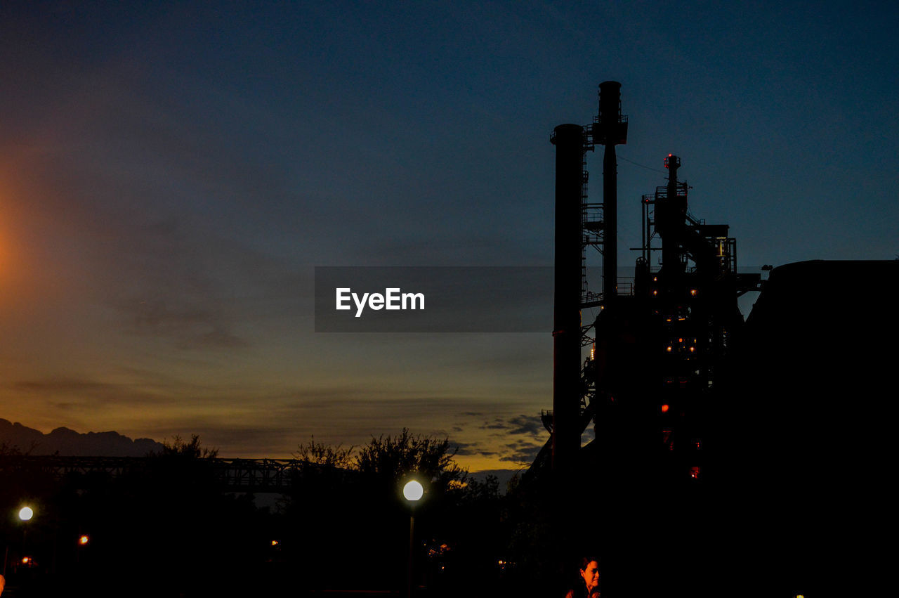 sky, industry, architecture, factory, built structure, silhouette, building exterior, no people, fuel and power generation, nature, illuminated, sunset, cloud - sky, orange color, outdoors, night, smoke stack, oil industry, low angle view, technology, industrial equipment