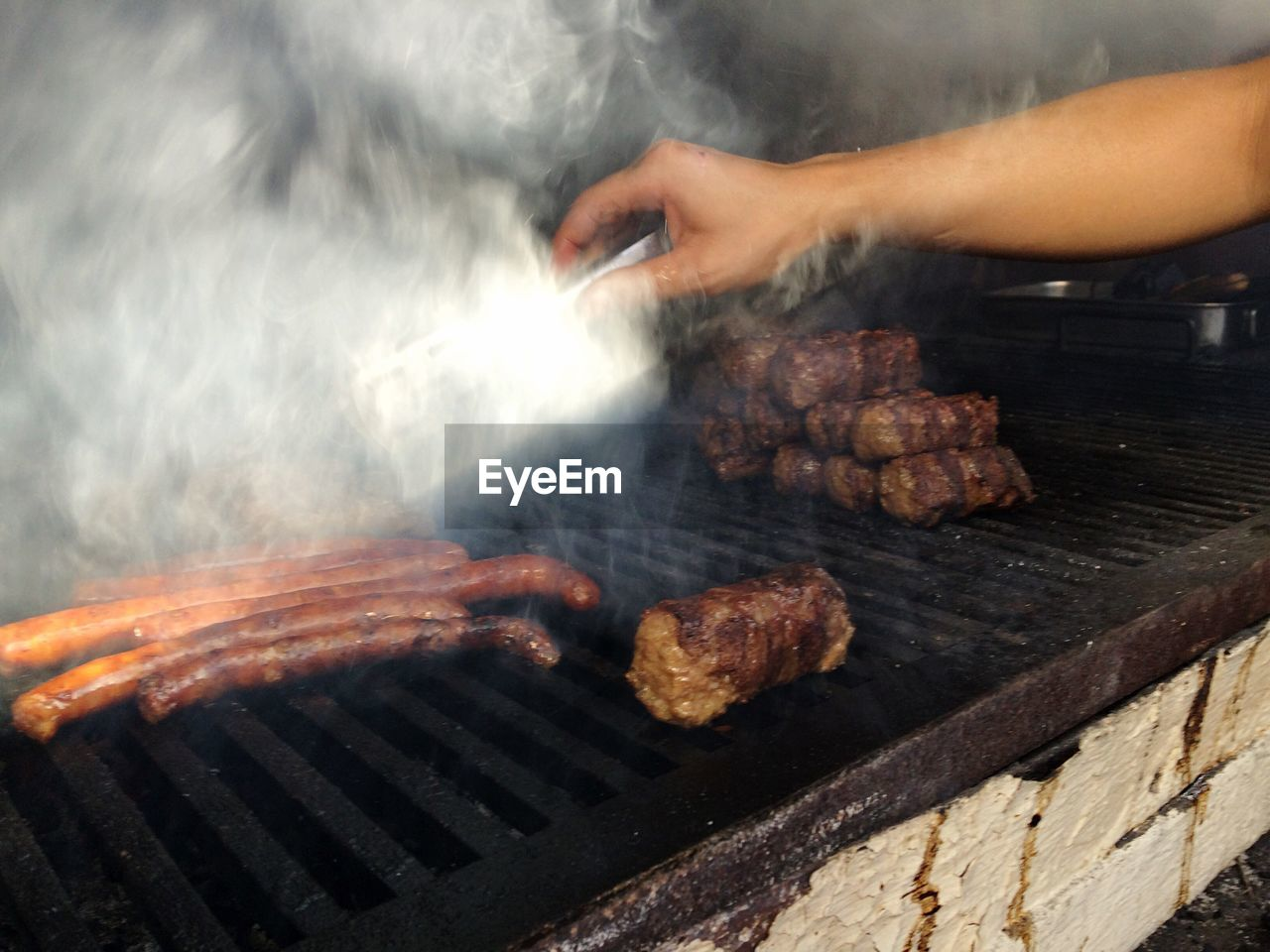 Cropped Image Of Hand Cooking Sausages On Barbeque