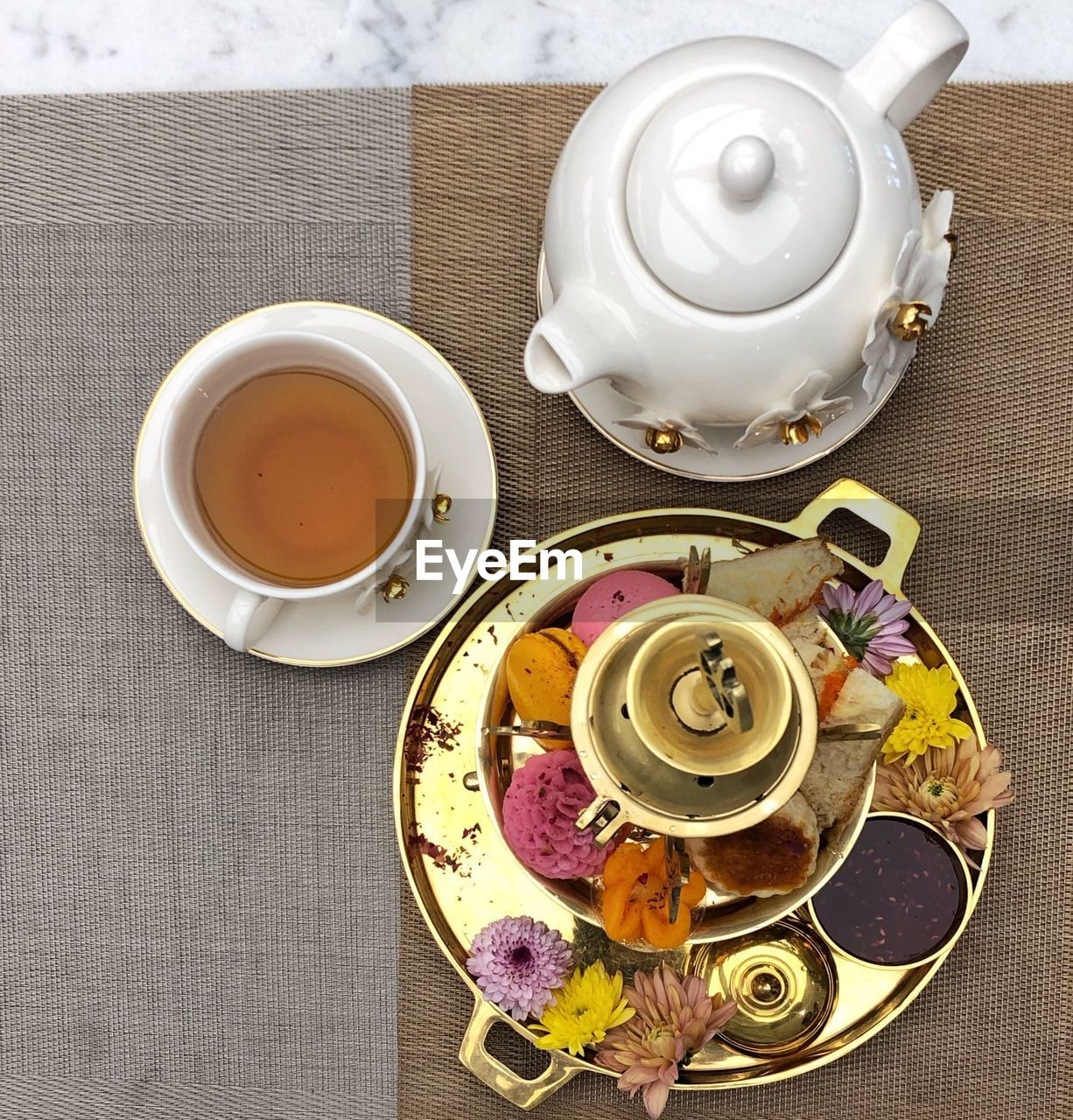 drink, food and drink, cup, refreshment, tea, teapot, tea - hot drink, mug, hot drink, tea cup, table, crockery, indoors, saucer, freshness, high angle view, directly above, food, still life, plate, no people, black tea, floral pattern, place mat, temptation