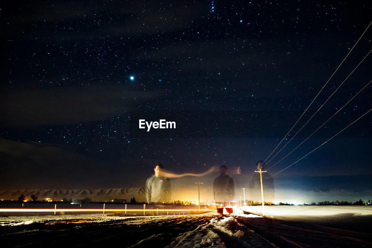 Multiple Exposure Image Of Man Standing On Street Against Star Field At Night