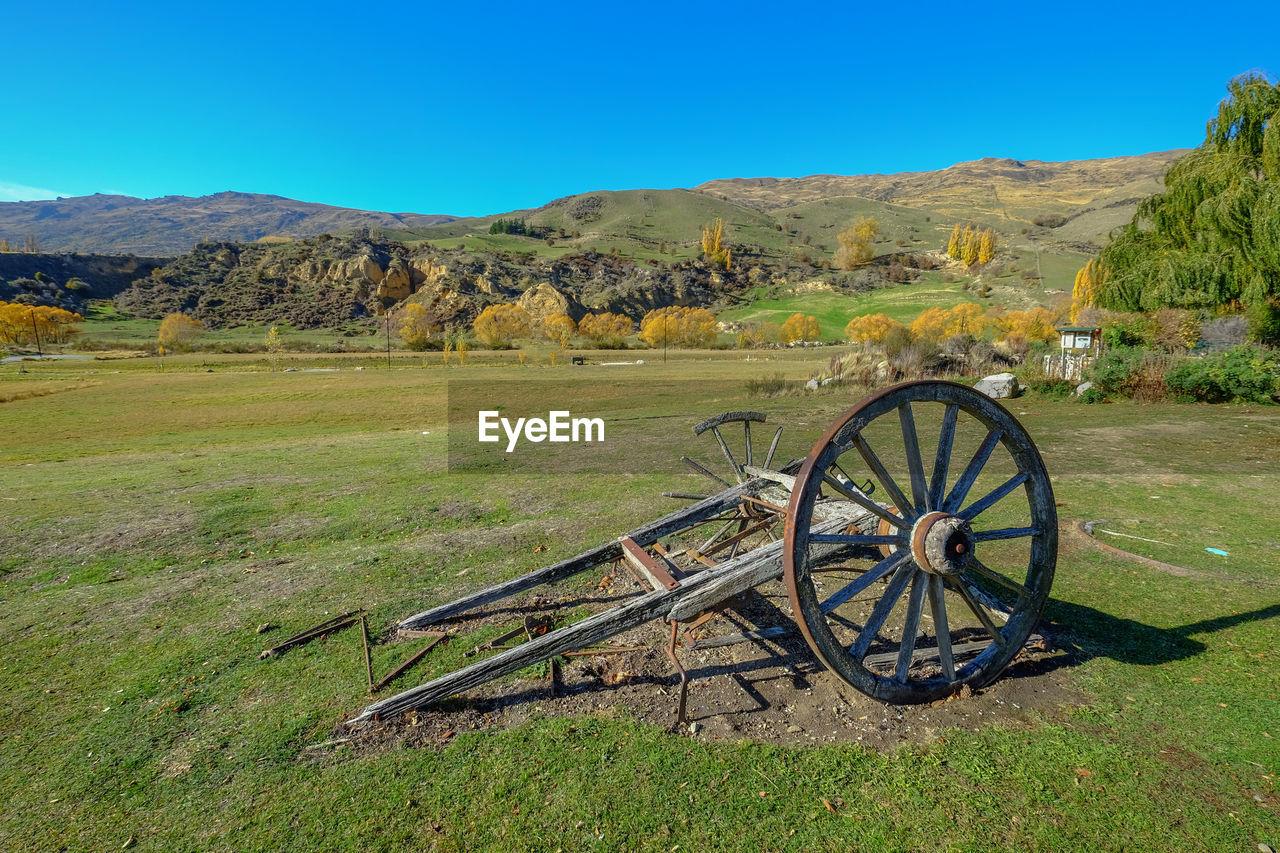 Wagon wheel on field against sky