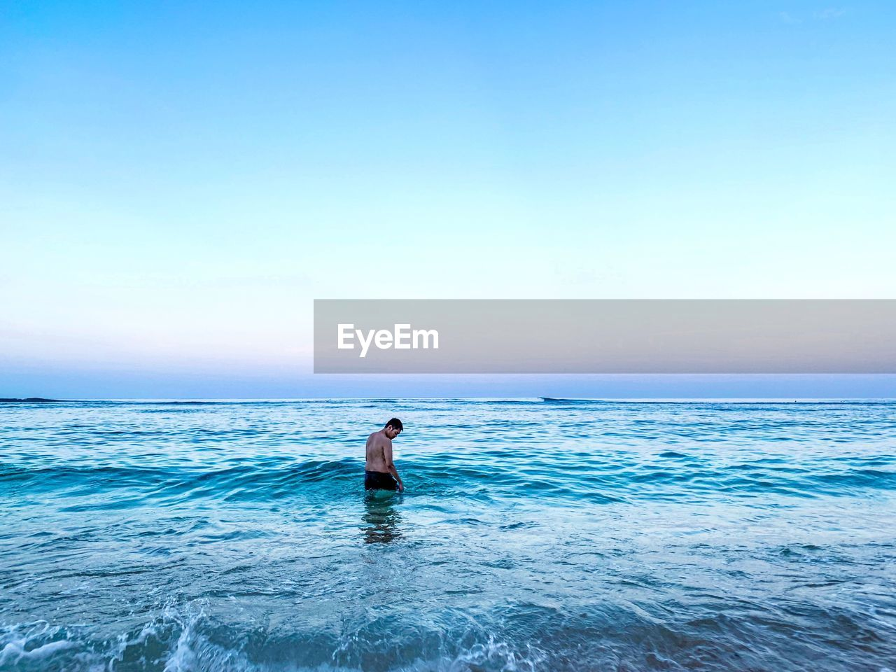 Shirtless man in sea against clear sky