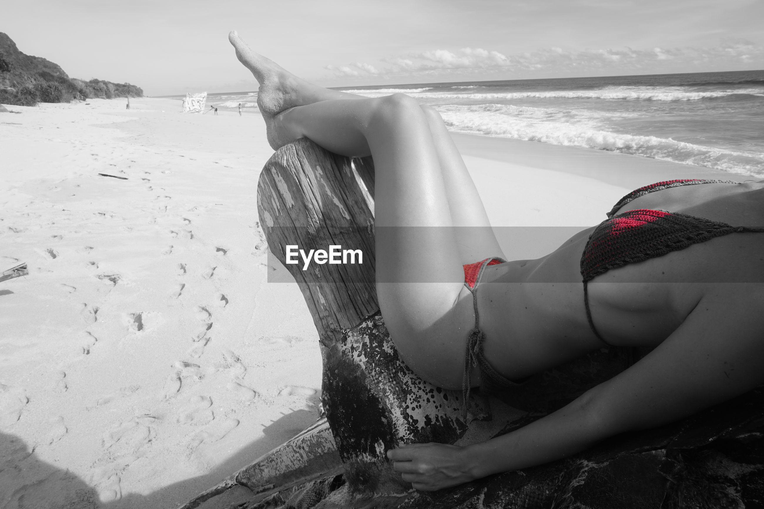 WOMAN ON BEACH AGAINST SEA