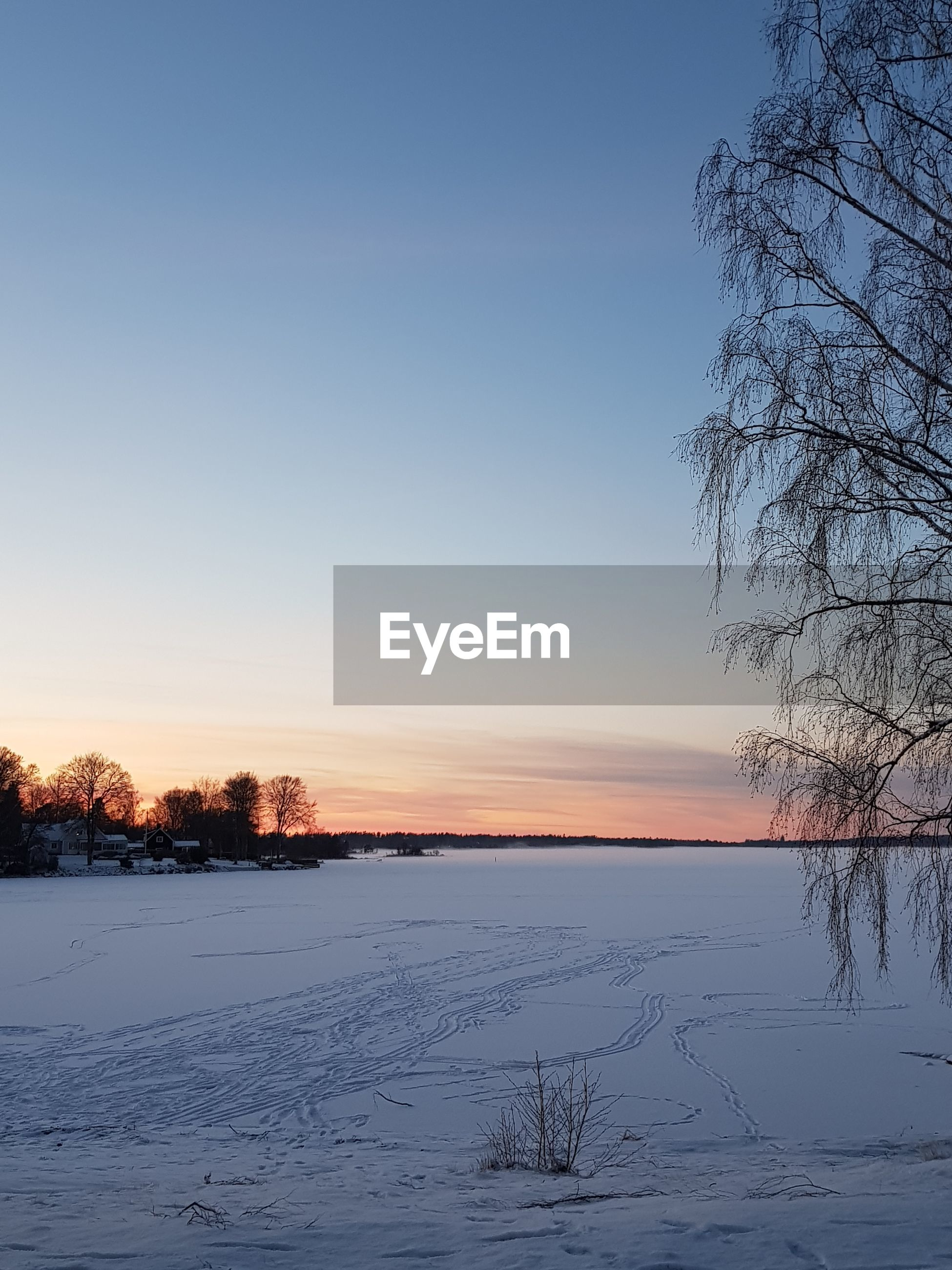 SNOW COVERED LANDSCAPE AGAINST SKY AT SUNSET