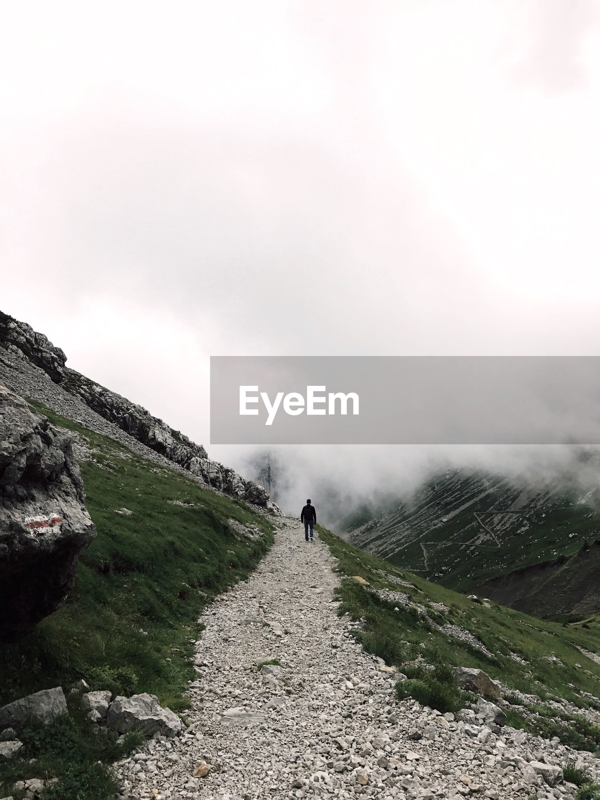 Rear view of man walking on footpath by mountain against sky